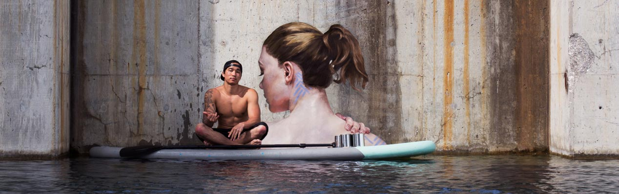 hula sitting on surfboard infront of watery mural