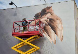 artist j3 on scissor lift painting mural of man jumping