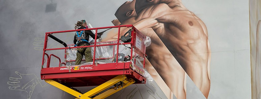 artist j3 on scissor lift painting mural of man jumping