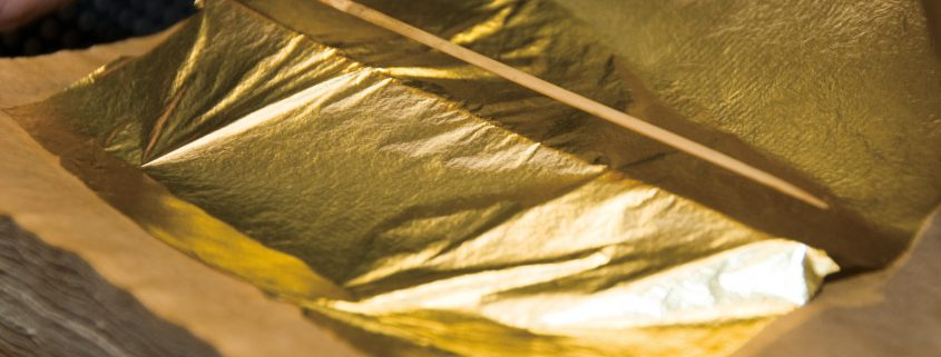 kanazawa gold leaf being produced, a hand using chop sticks to position the leaf is visible