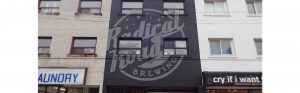 close up viewing the front of radical road brewing with large 3 storey custom hand painted sign visible