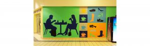 view of inside of shoppers world brampton with mural featuring a silhouette of a couple sitting and eating food with shopping bags at their feet