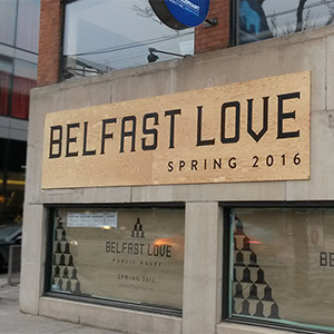 thumbnail of outside of belfast love during construction with custom painted sign on brick visible