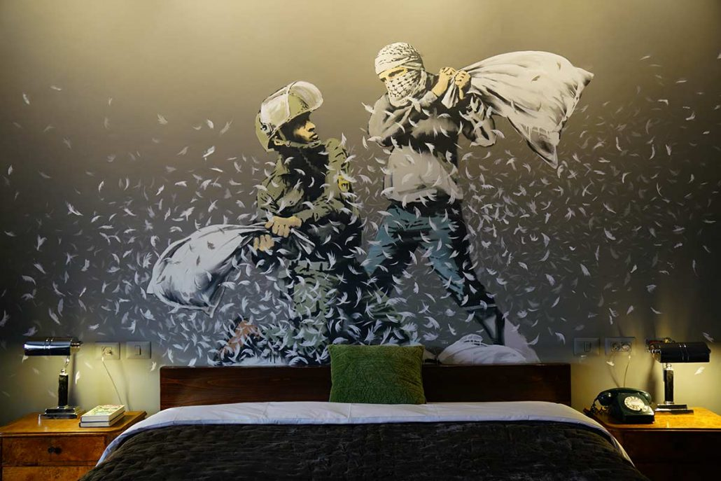 view of mural featuring ironic depiction of two men pillow fighting painted by banksy inside of the walled off hotel
